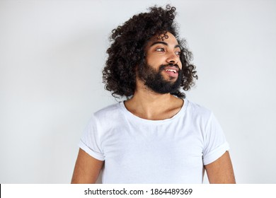 portrait of cheerful positive male of arabic appearance looking away laughing, he listen to joke, have fun with someone, isolated over white background