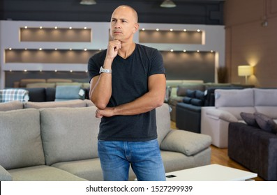 Portrait of cheerful positive male client in furniture salon shopping room with couches