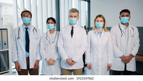 Portrait of cheerful positive multi-ethnic different healthcare professional doctors and physicians in medical masks stand in hospital clapping hands and applauding, covid quarantine concept