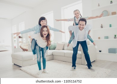 Portrait of cheerful positive parents playing with kids in modern white apartments holding on back in piggyback style, children making airplane open hands to the side. Aspiration imagination concept