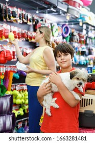 Portrait of cheerful positive smiling teen boy with his little dog visiting pet supplies shop with mother