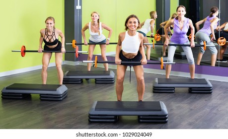 Portrait of  cheerful positive smiling women exercising with barbell in fitness club