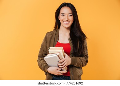 Portrait of a cheerful pretty asian girl holding books and looking at camera isolated over yellow background