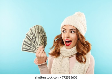 Portrait of a cheerful pretty girl dressed in hat and scarf looking at bunch of money banknotes isolated over blue background