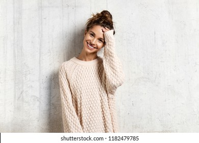Portrait of cheerful pretty smiling girl in cozy knitted sweater. Beauty and winter concept. Copy space in right side. Isolated on beige background
