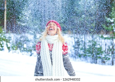 Portrait of cheerful pretty woman throwing snow in the air.  Winter holidays concept
