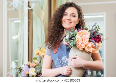 Portrait of cheerful pretty young woman florist holding vase with beautiful fresh flowers in shop