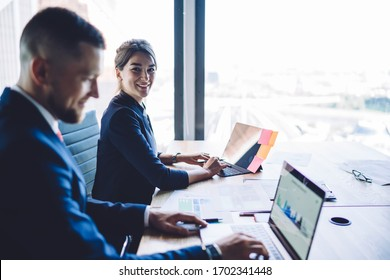 Portrait of cheerful proud ceo smiling at camera during cooperation with successful male colleague browsing financial website for checking banking exchange with infographics, business concept