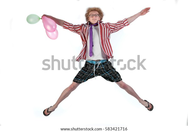 portrait of cheerful red-haired curly-haired young clown in glasses and striped shirt