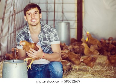 portrait of cheerful russian man farmer with chicken on poultry farm indoors