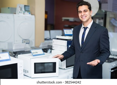 Portrait of cheerful sales manager showing goods at household appliances section