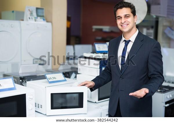 Retrato de alegre gerente de ventas mostrando bienes en la sección de electrodomésticos