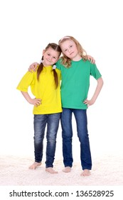 portrait of cheerful schoolgirls in colored T-shirts on white background