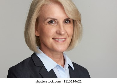 Portrait of cheerful senior businesswoman looking at camera. Middle aged executive woman smiling. Studio isolated