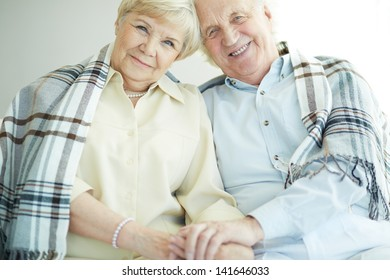 Portrait of cheerful senior couple looking at camera with smiles