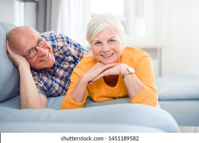Portrait of cheerful senior couple relaxing and lying on sofa at home