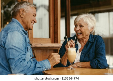 Portrait of cheerful senior couple sitting at table in cafe. Happy old couple talking and enjoying a cold coffee at cafe.