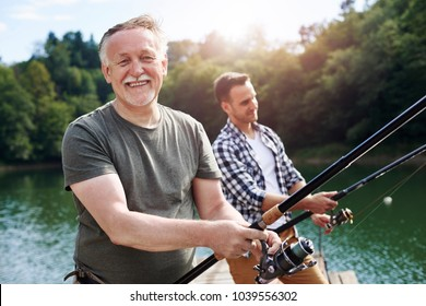 Portrait of cheerful senior man fishing