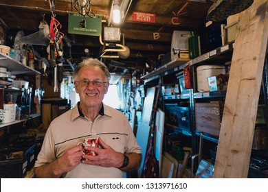 Portrait of a cheerful senior man in his workshop shed with a cup of tea.