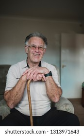 Portrait of a cheerful senior man with his walking stick in the living room of his home.
