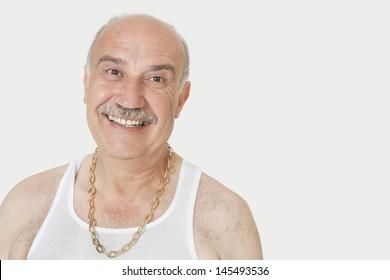 Portrait of cheerful senior man in vest over gray background