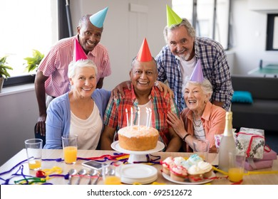 Portrait of cheerful senior people celebrating birthday at nursing home