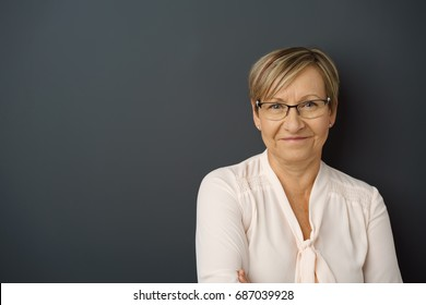 Portrait of cheerful senior woman leaning against dark wall
