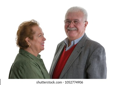 Portrait of cheerful senior woman looking at smiling elderly man against white background