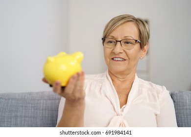 Portrait of cheerful senior woman sitting on sofa with piggy bank in hand