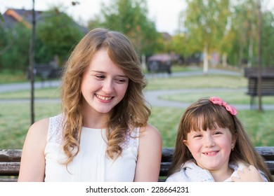 portrait of a cheerful senior and younger sister in the nature park
