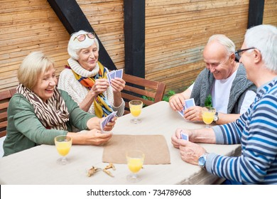 Portrait of cheerful seniors playing card game at lunch table on outdoor terrace  laughing happily