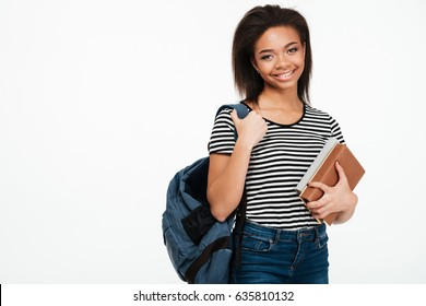 Portrait of a cheerful smiling african student girl wearing backpack and holding books isolated over white background