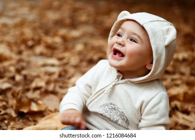 Portrait of a cheerful smiling baby having fun in autumn forest, sitting on the dry tree foliage, enjoying autumnal holidays