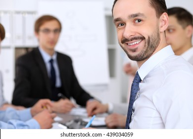 Portrait of cheerful smiling business man  at meeting.
