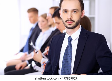 Portrait of cheerful smiling businessman  against a group of  people at meeting.