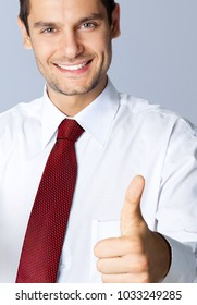 Portrait of cheerful smiling businessman with thumbs up gesture, against grey background