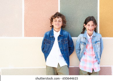 Portrait of cheerful smiling children in denim jackets and shirts over graphic painted wall. Copyspace.