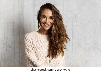 Portrait of cheerful smiling girl. Lovely girl with healthy dark hair posing isolated on beige background in warm sweater. Beauty and winter concept
