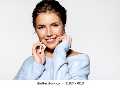 Portrait of cheerful smiling girl with perfect clean skin in fashionable sweater posing at studio. Beauty concept.