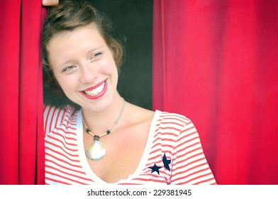 Portrait of a cheerful smiling happy young woman with dark hair and red lips. Vibrant red background.
