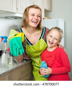 Portrait of cheerful smiling little daughter and mother tidy up at home kitchen