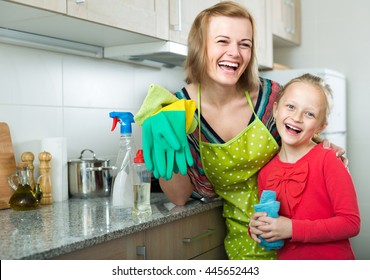 Portrait of cheerful smiling little girl and her mother tidy up at home kitchen