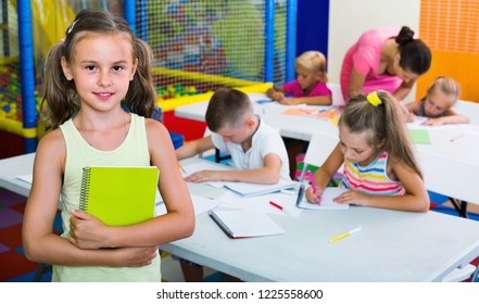 Portrait of cheerful smiling pupil girl studying in school class