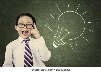 Portrait of cheerful smiling school student with lightbulb picture on blackboard