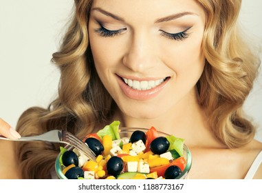 Portrait of cheerful smiling young blond woman eating vegetarian salad, against grey background. Healthy eating and dieting concept.