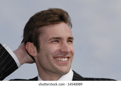 Portrait of  cheerful, smiling young businessman on  background of  sky