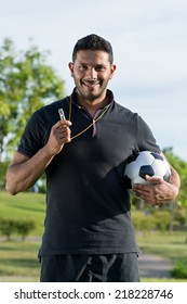 Portrait of cheerful soccer coach holding a ball