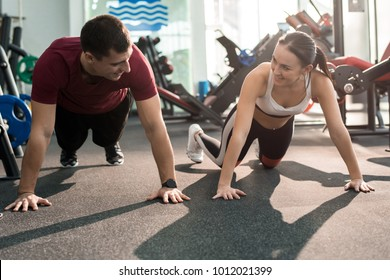 Portrait of cheerful sportive couple enjoying training in modern gym and smiling, looking at each other