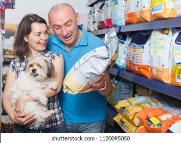 Portrait of cheerful spouses with dog buying vet food in petshop