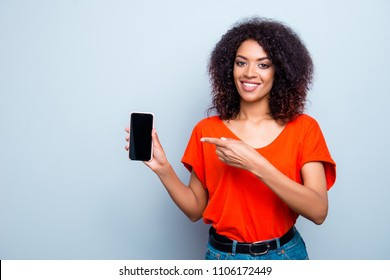 Portrait of cheerful stylish girl showing black touch screen of smart phone pointing with forefinger at copyspace empty place looking at camera isolated on grey background